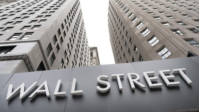 In this Aug. 31, 2020 file photo, buildings line Wall Street, in New York. The Dow Jones Industrial Average dropped 405.89 points, or 1.5%, to 27,534.58 on Thursday.