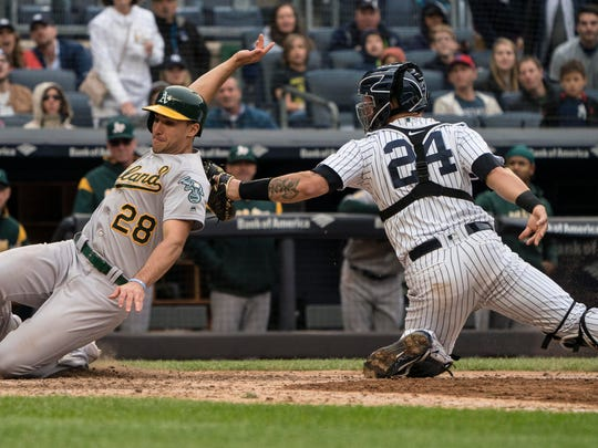 New York Yankees catcher Gary Sanchez (24) tags out Oakland Athletics first baseman Matt Olson (28) attempting to score on a sacrifice fly by Oakland Athletics catcher Jonathan Lucroy (not pictured) during the ninth inning of the game at Yankee Stadium on Saturday, May 12, 2018