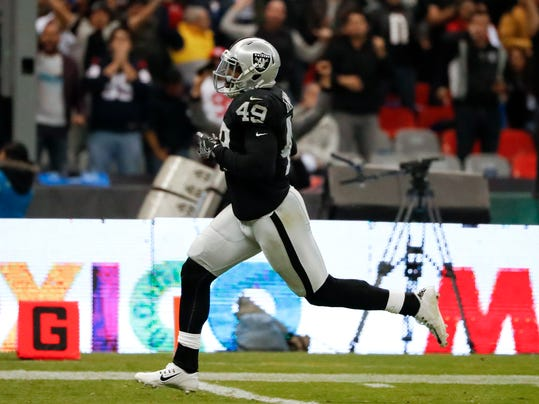 """FILE - In this Nov. 21, 2016, file photo, Oakland Raiders fullback Jamize Olawale scores a touchdown during the second half of an NFL football game against the Houston Texans in Mexico City. The Raiders' first trip to Mexico City offered a unique scene. With the Raiders set to make their return to Azteca Stadium on Sunday to take on the New England Patriots, the hope is that going through the experience a year ago will be beneficial this season. """"It's always an advantage to know where you're playing and what to expect,"""" Olawale said. """"I just remember the atmosphere and excitement was electric out there. It was awesome to see. It was like a true home game."""" (AP Photo/Eduardo Verdugo, File)"""