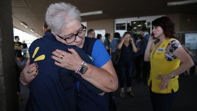 Employees comfort one another after a shooter opened fire at the Walmart near Cielo Vista Mall in El Paso on Aug. 3, 2019.