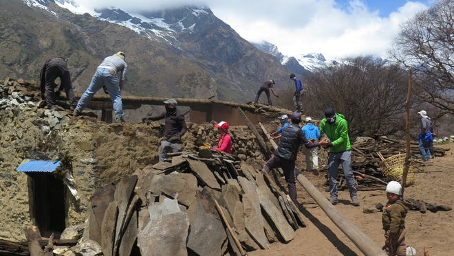 Climbers work to salvage raw materials by deconstructing a home in the Nepali village of Phortse that was damaged by an earthquake last month.