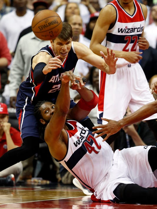Washington Wizards forward Nene (42), from Brazil, passes the ball after a struggle with Atlanta Hawks guard Kyle Korver, top left, in the second half of Game 6 of the second round of the NBA basketball playoffs, Friday, May 15, 2015, in Washington. The Hawks won 94-91 to advance to the next round. (AP Photo/Alex Brandon)