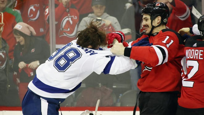Tampa's Mikhail Sergachev fights with New Jersey's Brian Boyle during the third period.