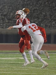 Muenster quarterback Parker McGrew (6) throws a first-half pass while Albany's Dax Neece pursues him in Friday's game in Iowa Park.  Muenster won the Region II-2A DII title game 28-12.