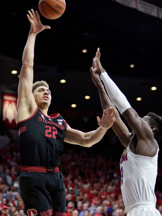 FILE - In this March 1, 2018, file photo, Stanford forward Reid Travis (22) shoots over Arizona forward Deandre Ayton during the first half during an NCAA college basketball game in Tucson, Ariz. Travis was selected to the AP All-Pac-12 team on Tuesday, March 6, 2018. (AP Photo/Rick Scuteri, File)