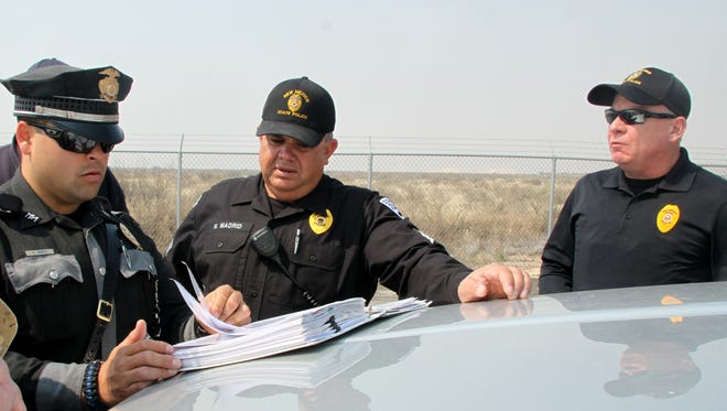 New Mexico State Police Patrolman Darian Jarrott, left, prepares for a mock inspection of a WIPP shipment with the help of instructors Sgt. Mark Madrid and Patrolman Jimmy White.