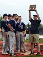 Lancaster High School principal Scott Burre holds up the 2018 Central District Division I trophy before handing it to the Golden Gales' baseball captains. Burre is a fixture at extra-curricular events.