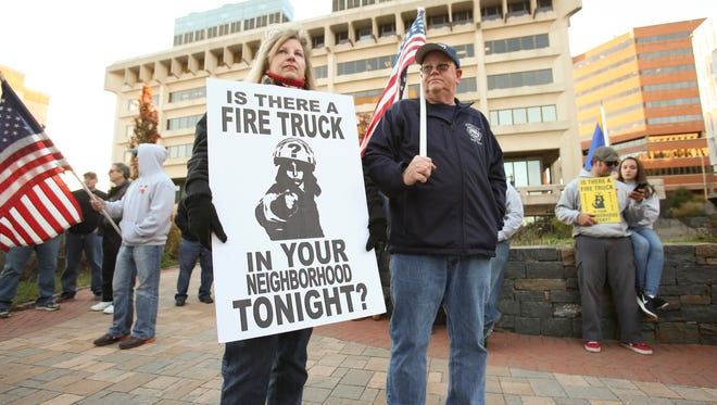 Susan Wiley and Wilmington Fire Department Capt. Kevin Turner stand with other fire department members and supporters as they gather opposite the Louis L. Redding City County Building Tuesday afternoon to protest the city's decision to resume a payroll savings plan by reducing the number of on-duty firefighters.