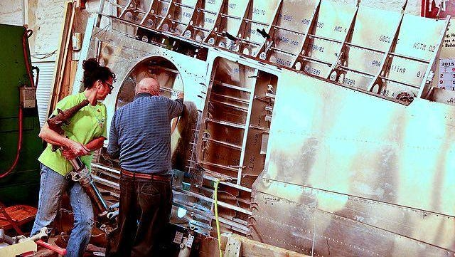 Volunteers examine the fuselage of a recovered Curtiss P-40 fighter at the Glenn Curtiss Museum in Hammondsport.