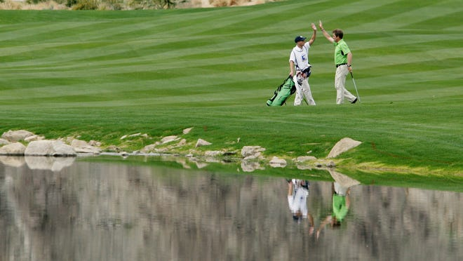 Singer Huey Lewis celebrates his eagle at the 18th hole with his caddy during the first day of the 50th annual Bob Hope Chrysler Classic golf tournament at SilverRock Resort in January 2009 in La Quinta.