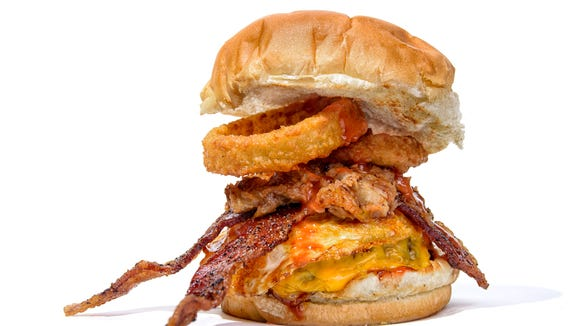 A burger piled high with toppings from Sickies Garage