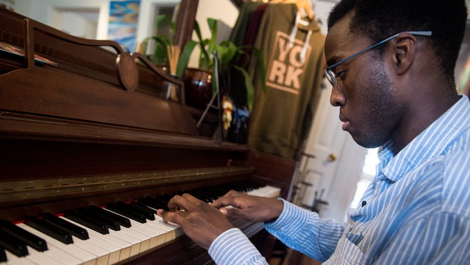Jason Wilson Kageni plays piano in his mother's shop, Gusa, on Philadelphia St., Tuesday, June 5, 2018. The Gusa World Music Festival is June 15-16 in York City. Tuesday, June 5, 2018. The Gusa World Music Festival is June 15-16 in York City.