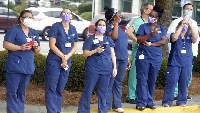 Masks are key to preventing the spread of COVID-19, researchers say. Masked hospital staff watch parachuters drop in at Memorial Hospital on Thursday morning.