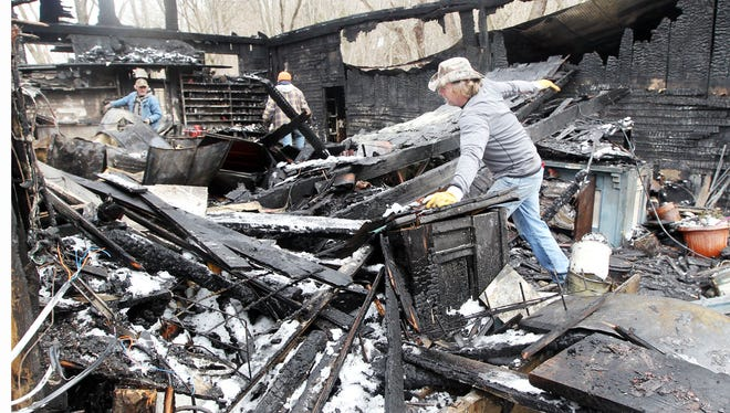 Volunteers clean debris from the site of a fire that heavily damaged the Rabbit Hash General Store.