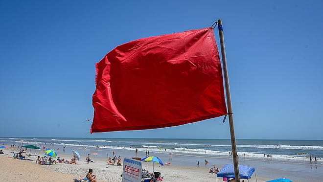 A red flag warns people of dangerous water conditions on St. Augustine Beach on Saturday. Later in the day, the county announced that swimming was prohibited, starting at 12:01 a.m. Sunday.