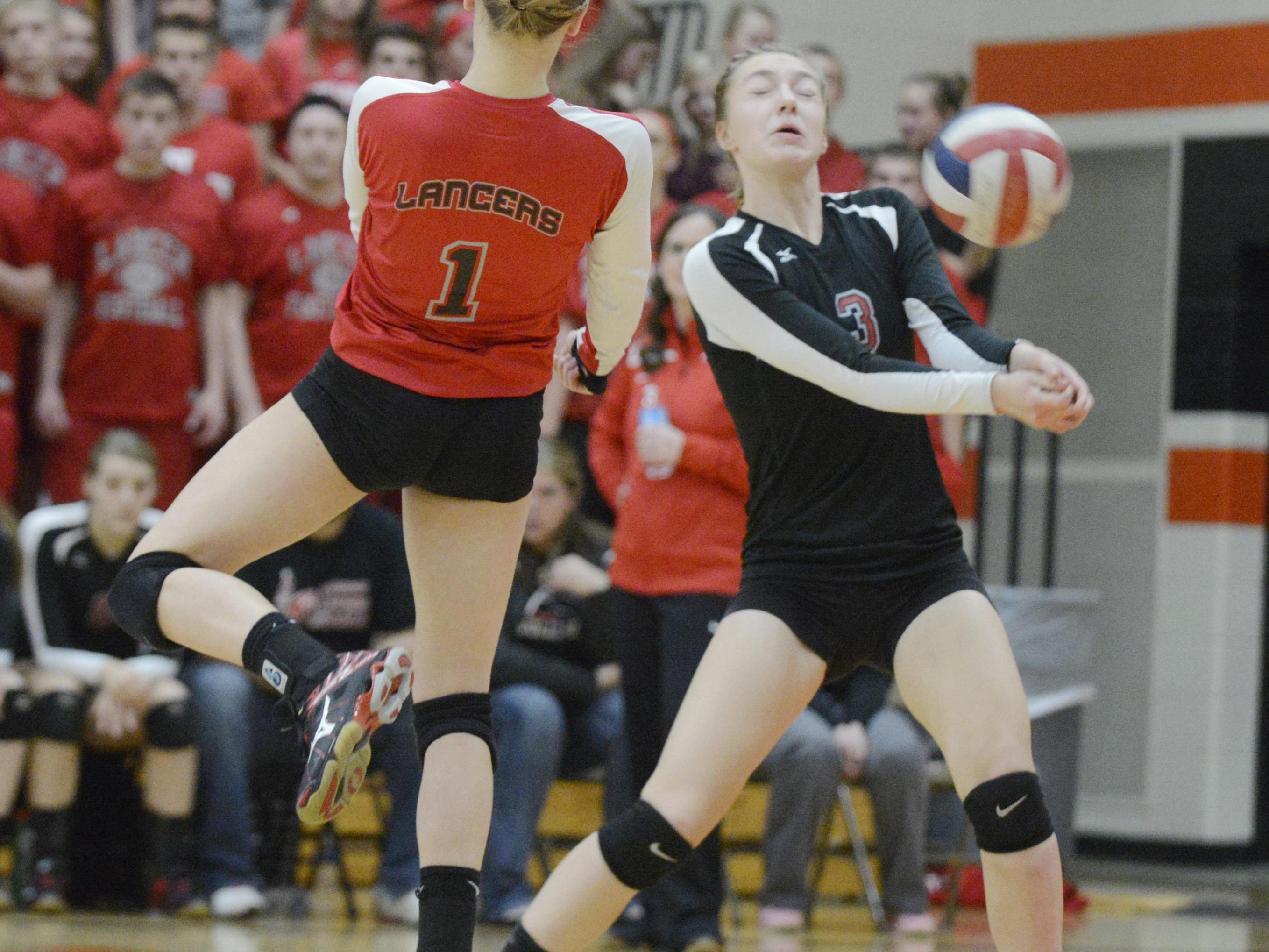Manitowoc Lutheran's Madeline Schleis, left, and Amanda Pautz both try to hit the ball during a game at the WIAA Division 3 Sectional Semifinals against Howards Grove at Reedsville Middle School on Thursday, Oct. 29 in Reedsville. The Lancers fell to the Tigers 3-0.