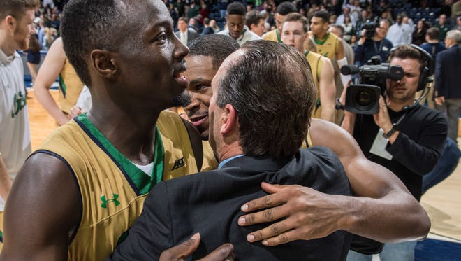 Dec 3, 2014; South Bend, IN, USA; Notre Dame Fighting Irish guard Jerian Grant (22) and guard Demetrius Jackson (11) hug head coach Mike Brey after Notre Dame defeated the Michigan State Spartans 79-78 in overtime at the Purcell Pavilion. Mandatory Credit: Matt Cashore-USA TODAY Sports
