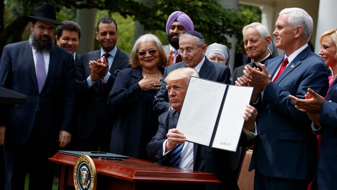 In this May 4, 2017, file photo, President Trump holds up a signed executive order aimed at easing an IRS rule limiting political activity for churches in the Rose Garden of the White House.