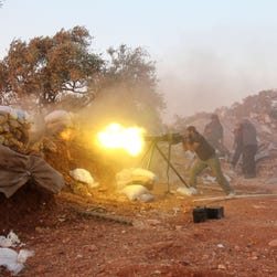 A rebel fighter fires heavy artillery during clashes with government forces and pro-regime shabiha militiamen in the outskirts of Syria's northwestern Idlib province on Sept. 18, 2015.