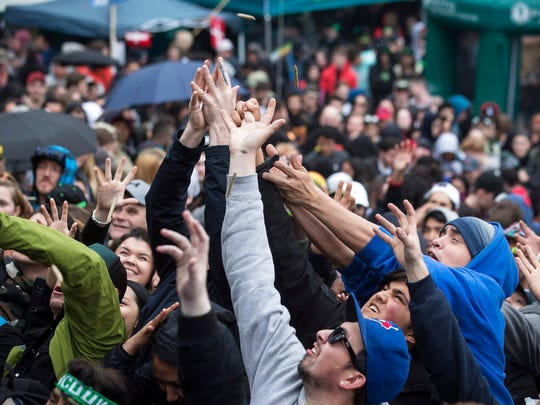 In this April 20, 2018 file photo, people reach for joints being thrown into the crowd during the 4-20 annual marijuana celebration, in Vancouver, British Columbia. Canada is following the lead of Uruguay in allowing a nationwide, legal marijuana market, although each Canadian province is working up its own rules for pot sales. The federal government and the provinces also still need to publish regulations that will govern the cannabis trade.