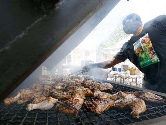 James Morgan of the Reggae Jamaica Restaurant and Bakery cooks chicken during the Rochester West Indian Festival Organization's Carifest at Dr. Martin Luther King Jr. Memorial Park at Manhattan Square.