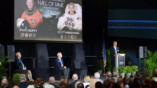 Dan Brandenstein, Chairman of the Astronaut Scholarship Foundation, and 2016 US Astronaut Hall of Fame inductee Brian Duffy listen as fellow inductee Scott Parazynski addresses the crowd Saturday at Kennedy Space Center Visitor Complex.