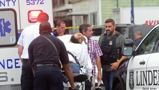 A man fitting the description of Ahmad Khan Rahami, 28, is loaded into the ambulance on East Elizabeth Avenue in Linden Monday morning.