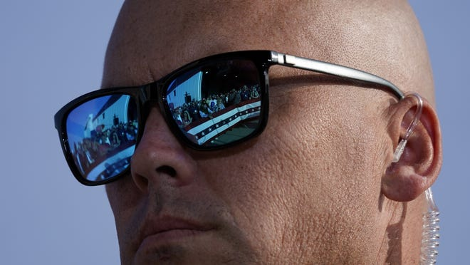 Supporters of President Donald Trump are reflected in the glasses of a U.S. Secret Service agent during a campaign rally at Dayton International Airport, Monday, Sept. 21, 2020, at Dayton, Ohio.