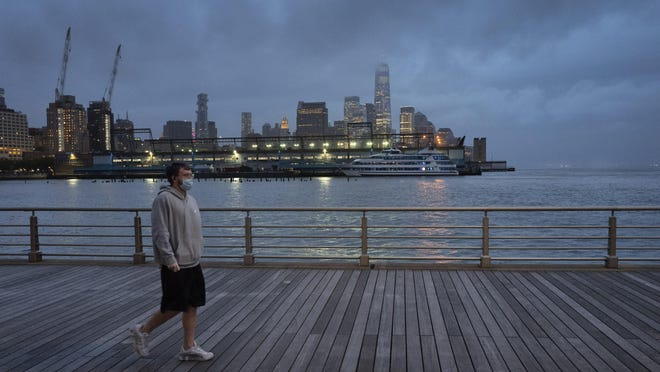 In this April 30, 2020, file photo, a man wears a face mask as he walks on Pier 45 in Hudson River Park in New York. The coronavirus pandemic has taken a harsh toll on the mental health of young Americans, according to a new poll that finds adults under 35 especially likely to report negative feelings or experience physical or emotional symptoms associated with stress and anxiety.