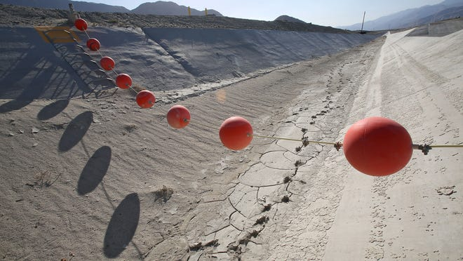 Buoys float over a dry canal that leads to the groundwater replenishment facility on the outskirts of Palm Springs. Imported water normally flows through the canal, but it has been largely dry during the drought.