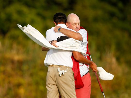 Caddie John Doherty, a Red Bank resident, hugs Stewart