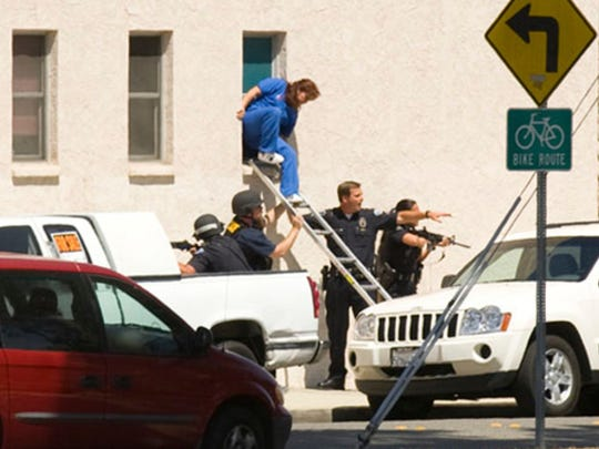 Simi Valley police help employees of a chiropractic/orthopedics office escape through a window during a shooting spree at the nearby Family Dental Care office on July 1, 2009.