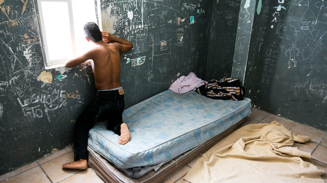 A teenage boy looks out the window of his sleeping area on June 19, 2014, at the Instituto Nacional del Migracion, a municipal shelter in Reynosa, Mexico, for child migrants that is receiving growing numbers of children caught by Mexican authorities and will be deported to their countries of origin.
