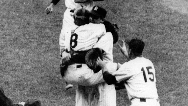 FILE - In this Oct. 8, 1956, file photo, New York Yankees catcher Yogi Berra (8) has jumped into the arms of pitcher Don Larsen after Larsen pitched the first perfect game in World Series history, defeating the Dodgers 2-0 at New York's Yankee Stadium.
