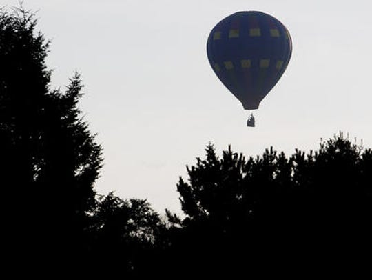A hot air balloon takes to the sky during the morning
