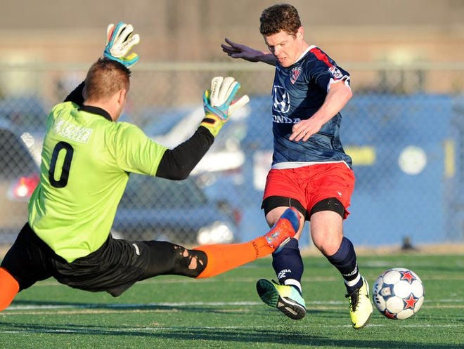 Indy Eleven forward Mike Ambersley (right) gets an assist on a goal past Tourbeau Soccer Academy goalkeeper Vignir Johannesson during an exhibition soccer game at Westfield High School. The Eleven, a first-year North American Soccer League team, made their debut in the Indianapolis area Saturday night.