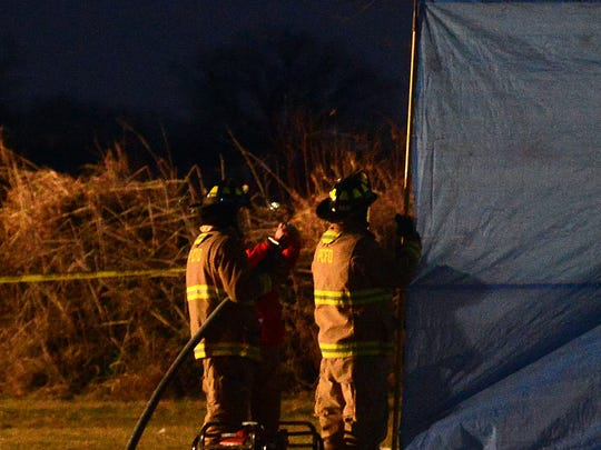 As night falls, firefighters tend to the scene after a plane crashed shortly after take off from the Erie Ottawa International Airport on Monday, Dec 29, 2014.