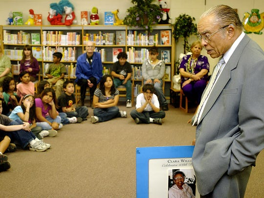 Students listen to Dr. James B. Williams, 89, talk about his mother, Clara Belle Williams, the first black woman to graduate from New Mexico State University, as he holds a picture of her Tuesday at University Hills Elementary. The World War II veteran, who served from 1942 to 1946 as a Tuskegee airman, described his life growing up when the United States was more segregated. The Las Cruces resident was invited in celebration of Black History Month, said Ginger McGuirk, school counselor.
