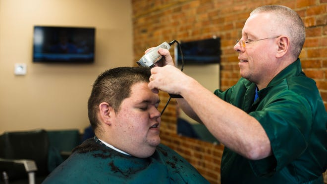 Mark Hughes talks about Florida weather and golf with a loyal customer while giving him his monthly trim on Thursday, Jan. 18, 2018, at Jerry's Barber Shop in Charlotte.