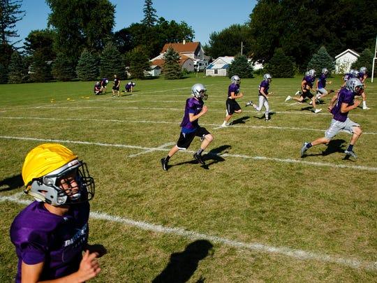 The Baxter Bolts football team runs sprints after practice