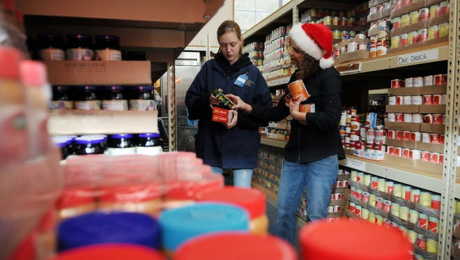 Kylee Burt (left) and Heidi Watts stock shelves at the Community Action Food Pantry in Lancaster.