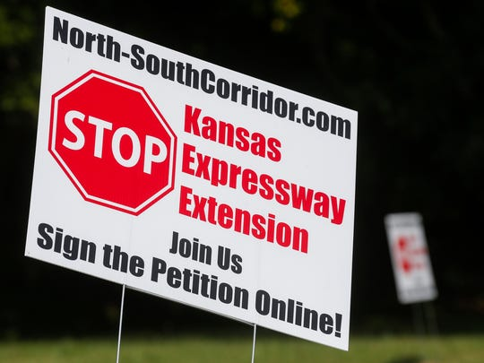 """A number of """"Stop Kansas Expressway Extension"""" signs can be seen on Farm Road 145 near the intersection with Weaver Road."""