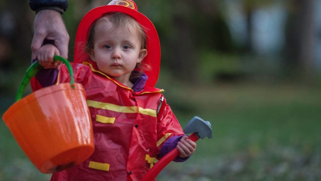 Families walk around the Reeveston neighborhood in Richmond to trick-or-treat on Halloween night, Tuesday, Oct. 31, 2017.