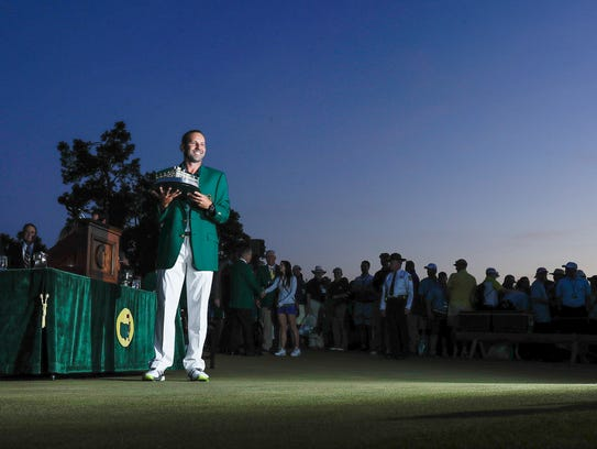 Sergio Garcia holds up his winning trophy at the green