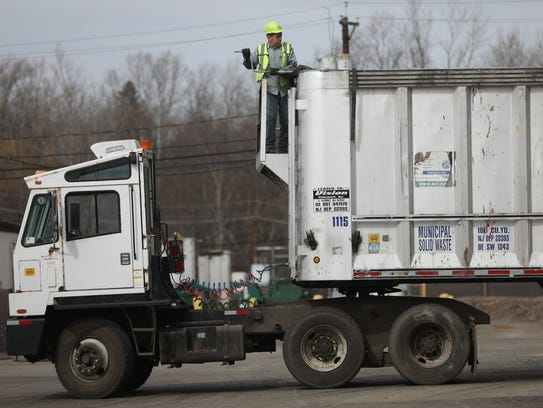 A man works on a truck, at the Waste Management Inc.