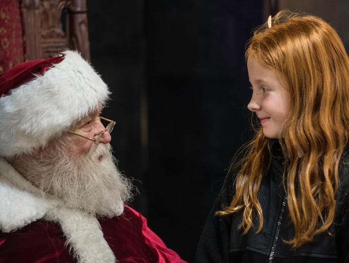 A girl tells Santa Claus what she wants for Christmas