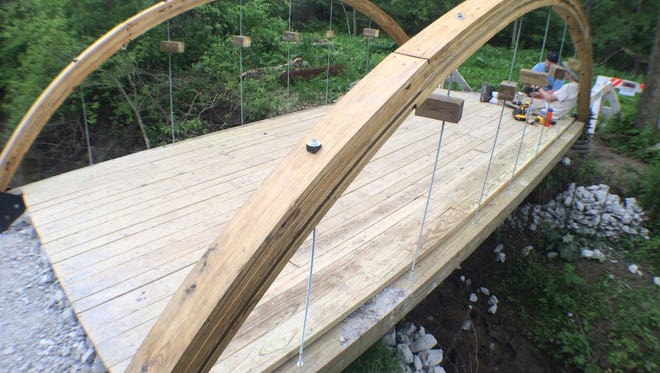 A bridge built by volunteers and Boy Scouts was nearly finished Saturday at Hickory Hill Park.
