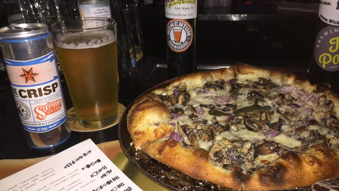The Truffle Shuffle is topped with black truffle oil, garlic, portabella mushrooms, Parmesan, mozzarella, pepper, red onion and sage. It's paired with The Crisp by Six Point Brewery.
