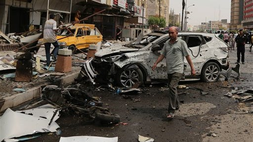 Civilians and security forces inspect the scene of a car bomb explosion in Karrada neighborhood, Baghdad, Iraq, Saturday, May 9, 2015. A car bomb exploded in Baghdad's central Karrada area, killing at least eight civilians and wounding dozens, a police officer said. Among the dead were Shiite pilgrims preparing for next week's major event commemorating the anniversary of the 8th century death of a revered religious figure, Imam Mousa al-Kazim. Thousands of pilgrims typically march to his shrine in northern Baghdad to commemorate his death. (AP Photo/Karim Kadim)