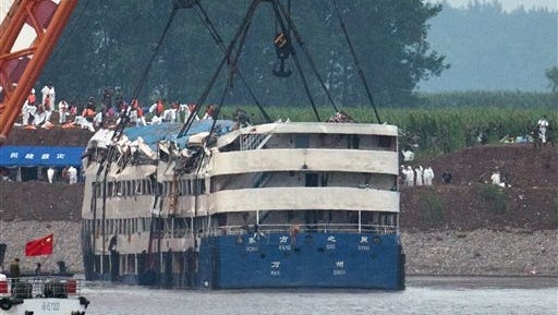 Medical workers make preparations near the capsized Eastern Star ship, as it is lifted by cranes on the Yangtze River in Jianli county of southern China's Hubei province, as seen from across the river from Huarong county of southern China's Hunan province, Friday, June 5, 2015. The Eastern Star's top-deck cabins with smashed blue roofs jutted out of gray water Friday after Chinese disaster teams righted the capsized river cruiser to ease the search for people still missing. (AP Photo/Andy Wong)